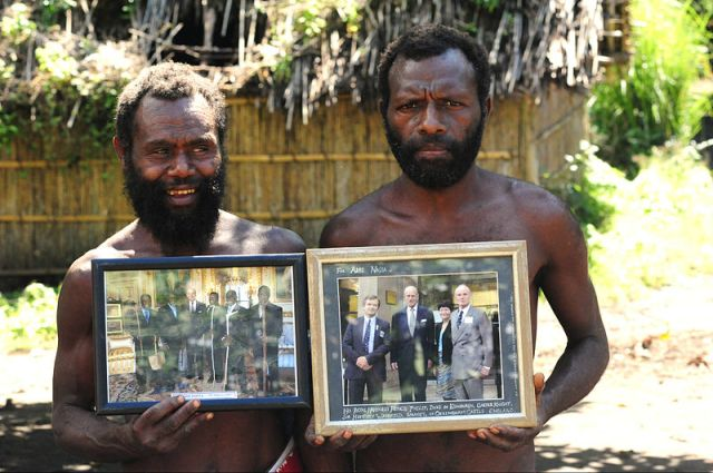 Two Yaohnanen Tribesmane proudly show off their photo of the 2007 royal visit with their god, Prince Philip. Photo by Christopher Thompson.