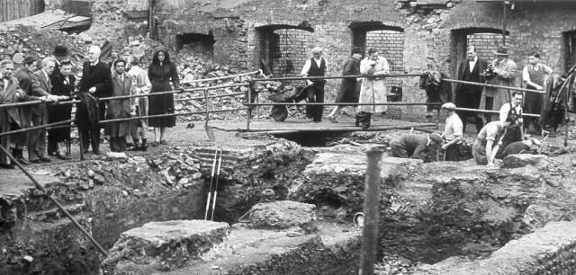Excavation of the Temple of Mithras in 1954 Photo by Ivor Noel Hume. The bombed out buildings of WW2 clearly visible in the background.