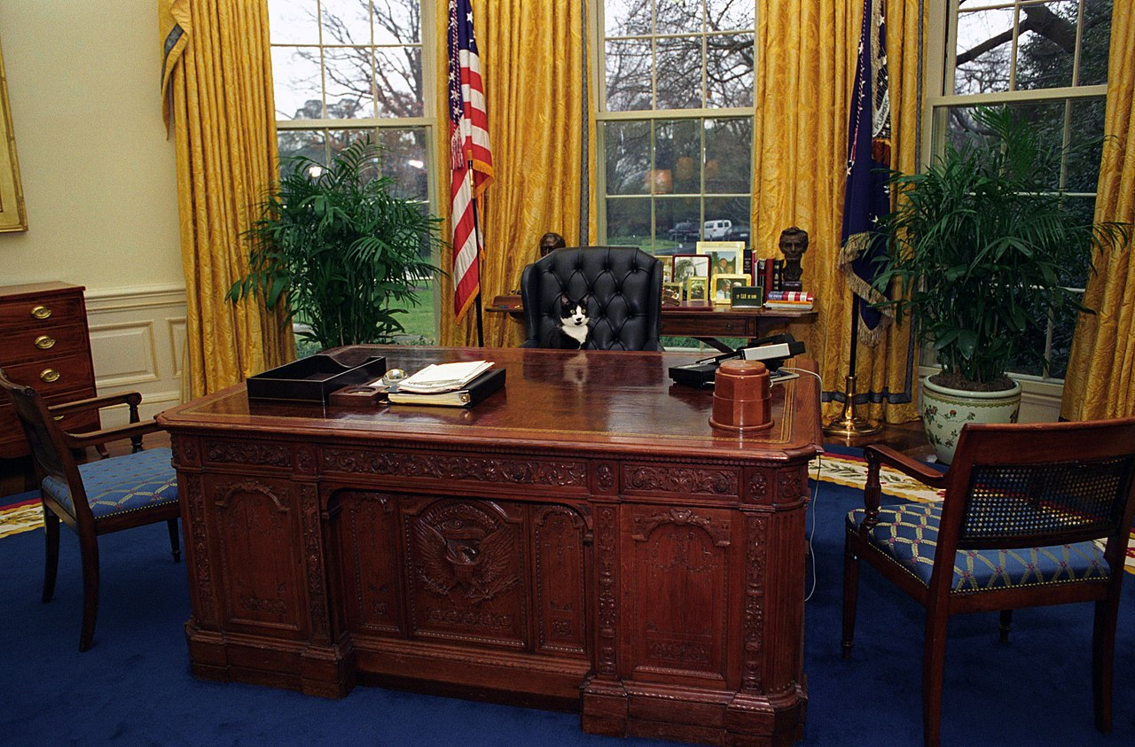 1280px-Photograph_of_Socks_the_Cat_Sitting_Behind_the_President's_Desk_in_the_Oval_Office-_01-07-1994_(6461515323)
